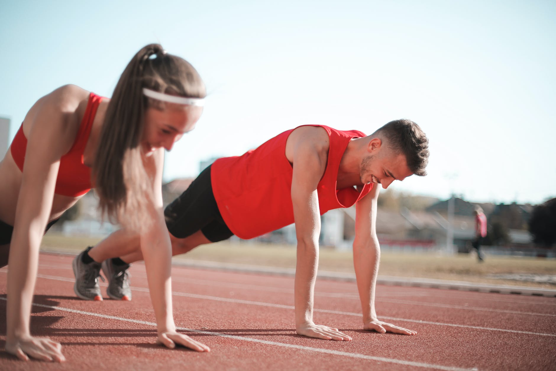 man and woman in red tank top and black shorts doing yoga